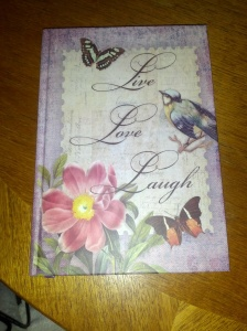 Notebook cover with butterflies and birds and a 'Live, Love, Laugh' motif.